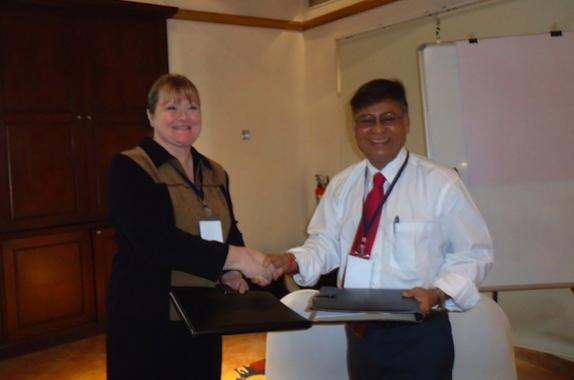 Shri Hirak Dutta and Ms. Louisa Nara exchanging the signed MOU folders.