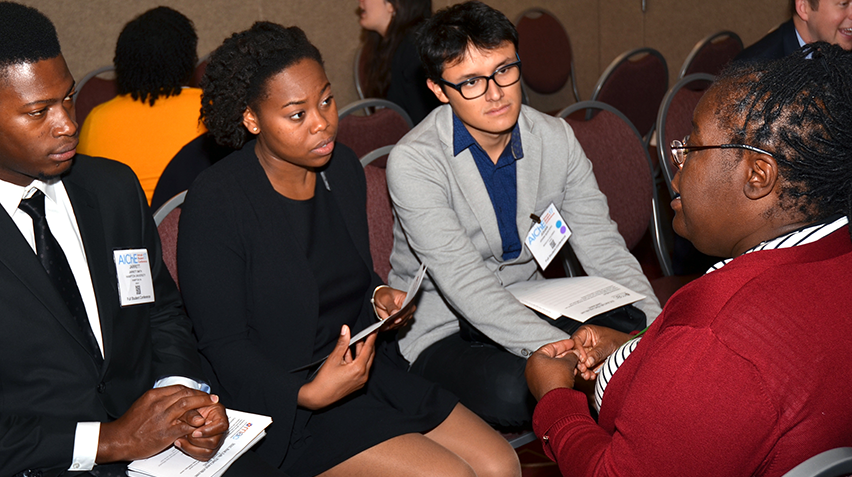 Kathy Lee (right) speaks with chemical engineering students at an industry event.